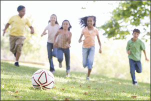 School age children playing soccer